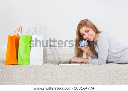 Portrait Of Smiling Young Woman Shopping Online Holding Credit Card - stock photo