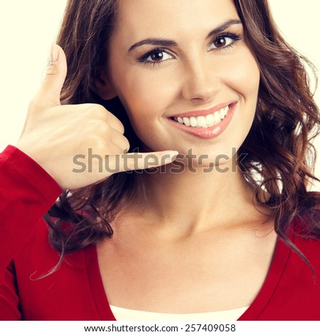 Portrait of smiling young woman showing call me gesture - stock photo