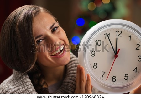 Portrait of smiling young woman showing clock in front of Christmas lights - stock photo