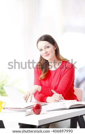 Portrait of smiling young woman sitting at desk and working from home. - stock photo