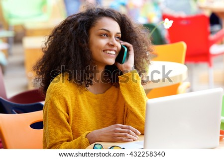 Portrait of smiling young woman sitting at outdoor coffee shop talking on mobile phone