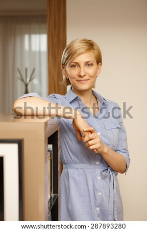 Portrait of smiling young woman standing at home, looking at camera. - stock photo