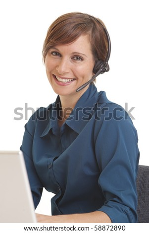 Portrait of smiling young woman telemarketer at computer desk - stock photo