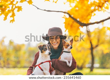 Portrait of smiling young woman with dogs outdoors in autumn - stock photo