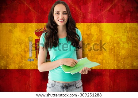Portrait of smiling young woman with file against spain flag in grunge effect - stock photo