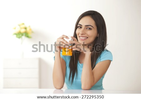 Portrait of smiling young woman with glass of orange juice at home - stock photo