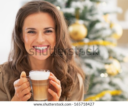 Portrait of smiling young woman with latte macchiato near christmas tree