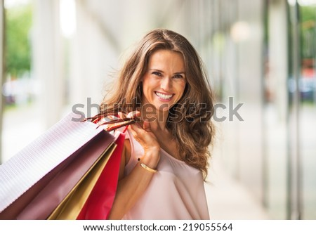 Portrait of smiling young woman with shopping bags - stock photo