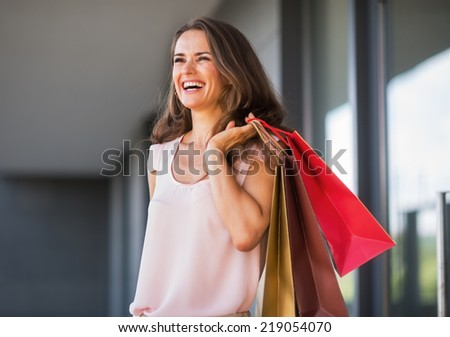 Portrait of smiling young woman with shopping bags on the mall alley