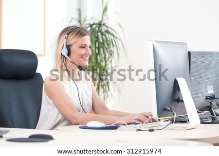 Portrait of smiling young woman working on a computer in a call center - stock photo