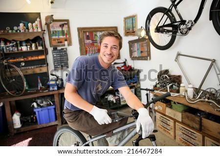 Portrait of smilng craftsman in bike workshop - stock photo