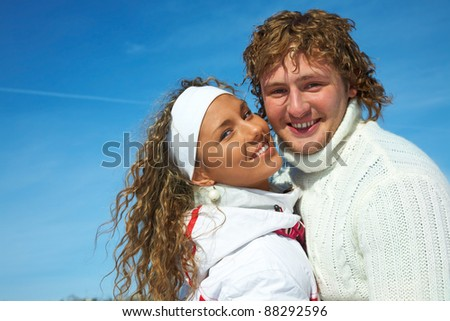 Portrait of smilyng young couple in winter park - stock photo