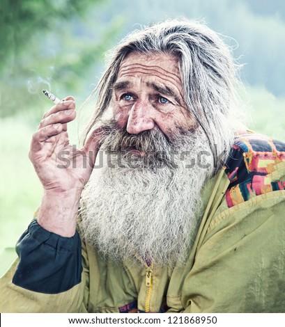 portrait of smoking old man with gray beard - stock photo