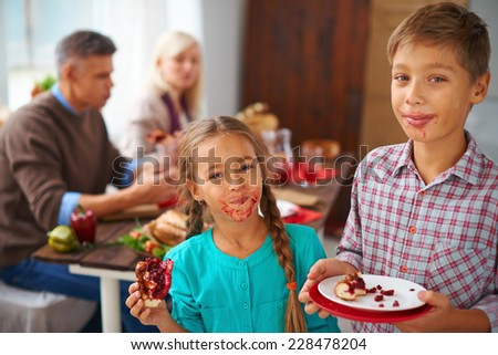 Portrait of smudgy siblings eating sweet pie and looking at camera with their parents on background - stock photo