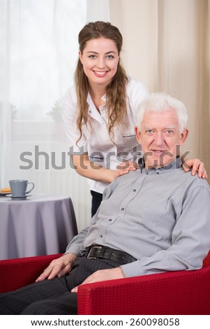 Portrait of social care worker and senior man - stock photo