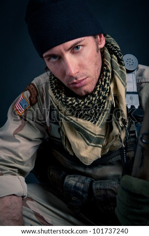 Portrait of soldier against black background. - stock photo