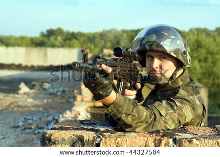 Portrait of soldier in camouflage with machine gun