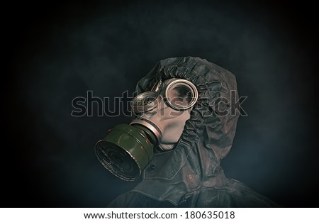 Portrait of soldier in chemical protection armor and gas mask looking up - stock photo
