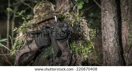portrait of soldier wearing camouflage, in wood, aiming with automatic weapon - stock photo