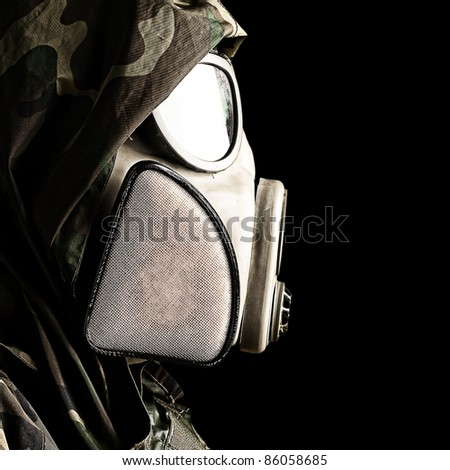portrait of soldier with gas mask against a black background