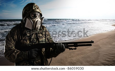portrait of soldier with gas mask walking in the beach holding a shotgun