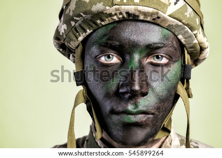 Portrait of soldier with painted face on grey background, close up view