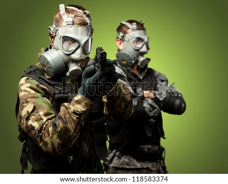 Portrait Of Soldiers With Gun And Gas Mask Against Green Background - stock photo