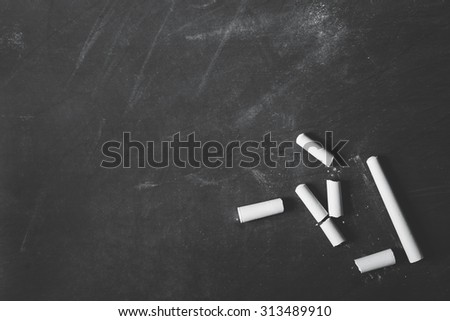 portrait of some white chalks on blank black board with copy space - stock photo