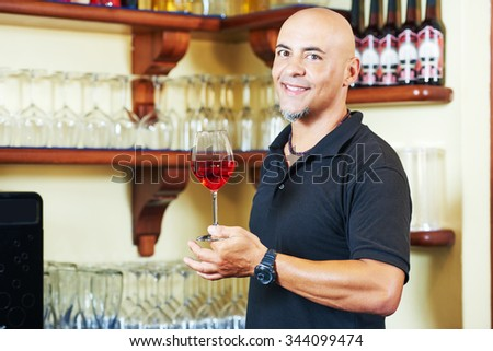 Portrait of sommelier barman holding a glass of water with wine glasses in the bar background - stock photo