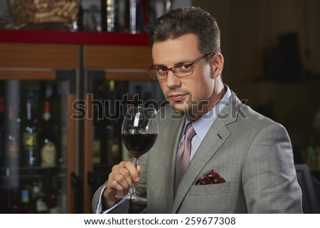 Portrait of sophisticated confident wealthy gentleman in stylish suit toasting with glass of wine against blurred restaurant background. - stock photo