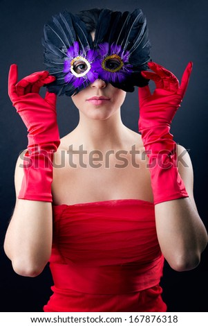 Portrait of Sophisticated woman with red dress and carnival mask - stock photo