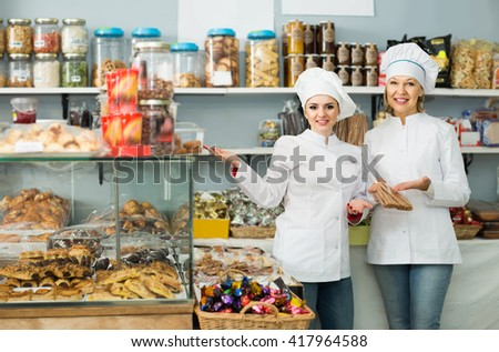 Portrait of spanish  female baker with pastry smiling in bakery - stock photo