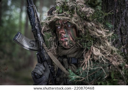 portrait of special forces soldier dressed in ghillie suit, hidden behind tree, holding assault rifle - stock photo