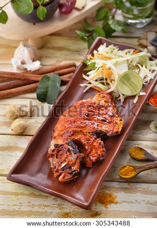portrait of spicy indian tandoori pomfret served with salad - stock photo