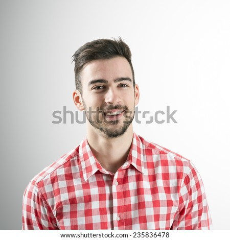 Portrait of spontaneous smiling positive young bearded man over gray background. - stock photo