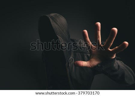 Portrait of spooky hooded unrecognizable person without face in dark room - stock photo