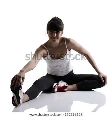 portrait of sport girl doing yoga stretching exercise, studio shot in silhouette technique over white background - stock photo
