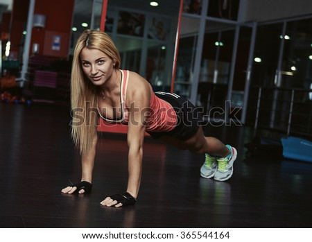 Portrait of sportive female doing push ups indoors in the gym. Young attractive fitness trainer  working out at aerobics class. - stock photo