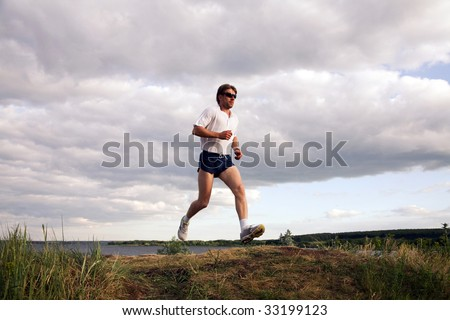 Portrait of sportsman doing exercise in the evening - stock photo