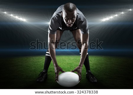 Portrait of sportsman holding ball while playing rugby against rugby stadium - stock photo