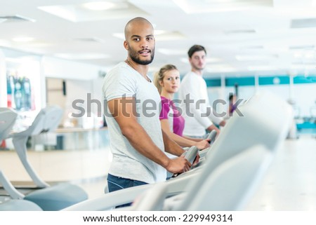 Portrait of sportsman in the gym. Young smiling man runs on a treadmill. - stock photo