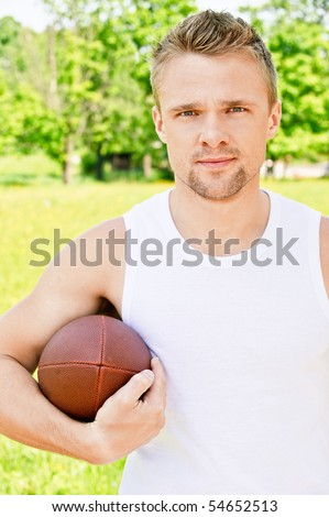 Portrait of sportsman of Rugby football against green summer nature.