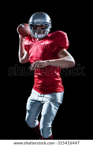 Portrait of sportsman throwing American football against black background