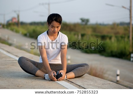 Portrait of sporty Asia woman sitting stretching exercises in roadside. Female athlete preparing for jogging outdoors. Runner doing side lunges. Full length