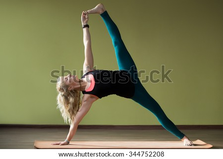 Portrait of sporty beautiful blond woman in sportswear working out indoors, doing advanced variation of Side Plank Posture, Vasisthasana on orange eco mat, strengthening arms, belly, legs, full length - stock photo