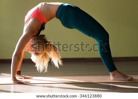 Portrait of sporty beautiful blond young woman in sportswear working out in gym, doing backbend, Bridge Pose, Urdhva Dhanurasana (Upward Bow), Chakrasana (Wheel) posture on orange mat, full length - stock photo