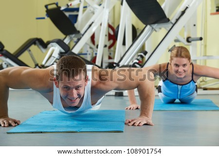 Portrait of sporty couple doing physical exercise and smiling at camera - stock photo