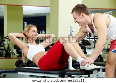 Portrait of sporty female doing physical exercise and interacting with her trainer - stock photo