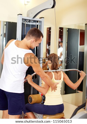 Portrait of sporty female doing physical exercise with young trainer helping her