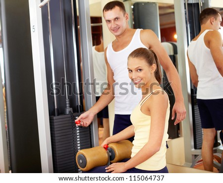 Portrait of sporty female in gym with young trainer near by